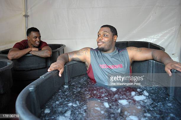 Washington Redskins' rookie Wide receiver Darius Hanks left talks with Defensive lineman Chris Baker right as they sit in tub of ice cooling off...