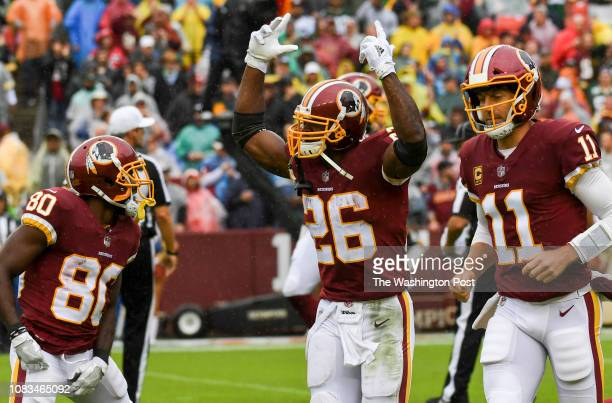 Washington Redskins running back Adrian Peterson center with Washington Redskins quarterback Alex Smith right and Washington Redskins wide receiver...