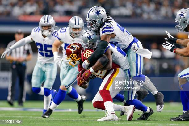 Washington Redskins Running Back Adrian Peterson is tackled by Dallas Cowboys Linebacker Jaylon Smith and Cornerback Jourdan Lewis during the NFC...