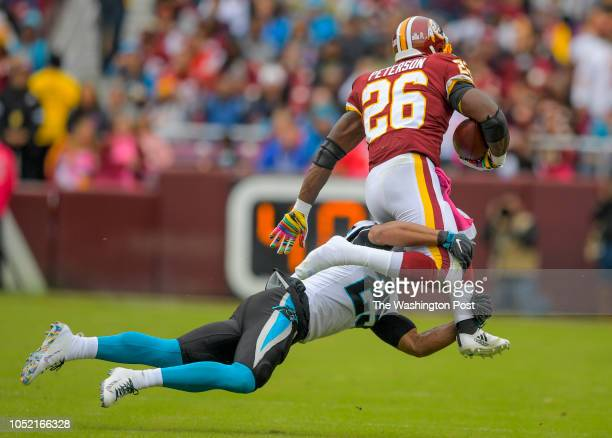 Washington Redskins running back Adrian Peterson is tackled by Carolina Panthers strong safety Eric Reid in the first half during a game between the...