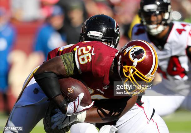 Washington Redskins running back Adrian Peterson rushes upfield before being tackled during the game between the Atlanta Falcons and the Washington...