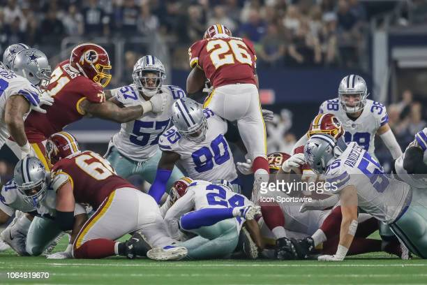 Washington Redskins running back Adrian Peterson steps over the line of scrimmage and gets tackled by Dallas Cowboys defensive end Demarcus Lawrence...