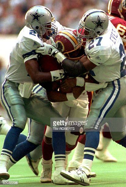 Washington Redskins running back Brian Mitchell is wrapped up by Dallas Cowboy defenders Kevin Smith and Thomas Everett during the first half action...