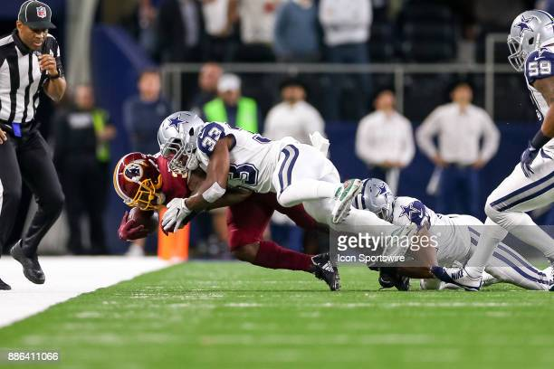 Washington Redskins running back Byron Marshall is tackled by Dallas Cowboys cornerback Chidobe Awuzie and safety Byron Jones during the Thursday...