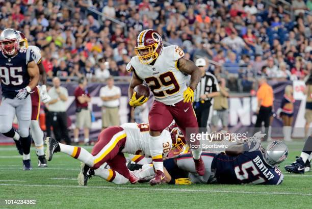 Washington Redskins running back Derrius Guice breaks through the line during a preseason NFL game between the New England Patriots and the...