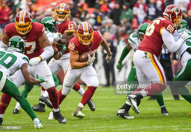 Washington Redskins running back Derrius Guice hits a hole made by offensive linemen Ereck Flowers and Tony Bergstrom during action against the New...