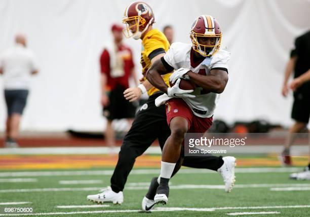Washington Redskins running back Mack Brown receives a handoff from Washington Redskins quarterback Colt McCoy during an OTA practice session on May...