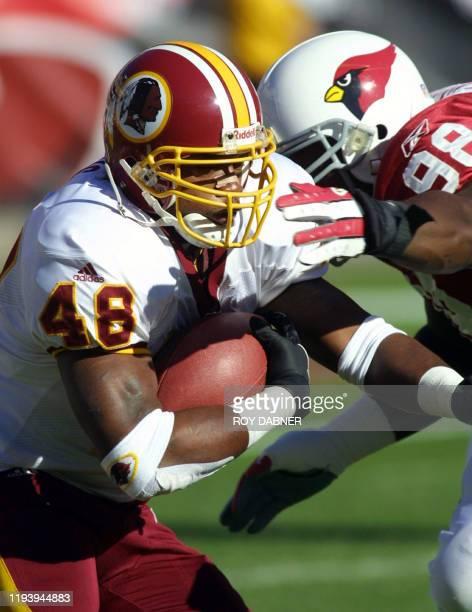 Washington Redskins' running back Stephen Davis runs through Arizona Cardinals' Russell Davis during the first quarter of their NFL game 09 December...