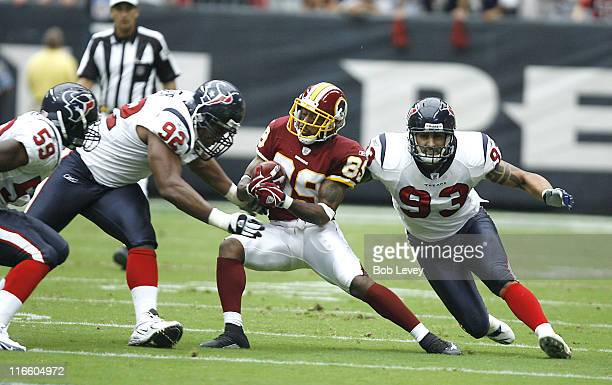 Washington Redskins wide receiver Santana Moss is tackled by Houston Texans defensive end Anthony Weaver and Houston Texans defensive end Jason Babin...