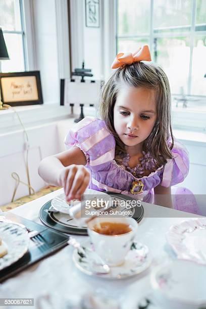 USA, Washington, Seattle, Girl (4-5) eating cookies at dining table