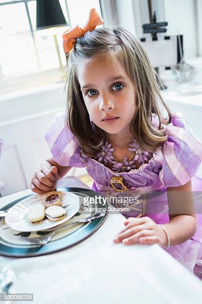 USA, Washington, Seattle, Girl (4-5) eating cookies at dining table