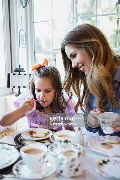 USA, Washington, Seattle, Mother and daughter (4-5) eating together in dining room