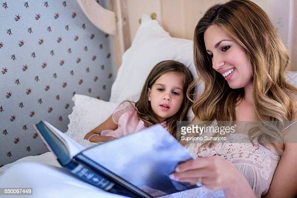 USA, Washington, Seattle, Mother reading bedtime story to her daughter (4-5)
