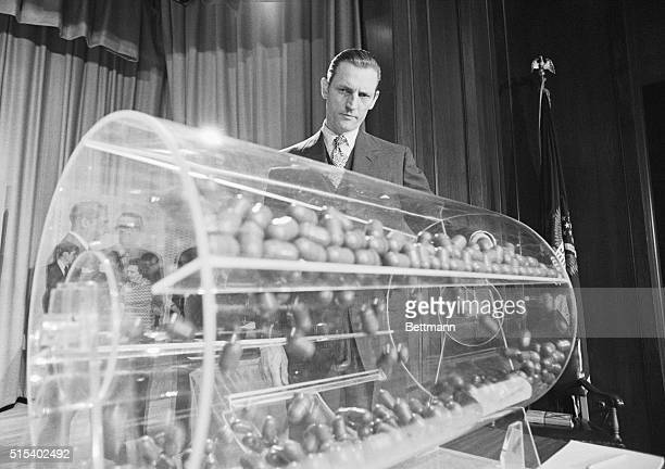 Selective Service Director Curtis Tarr spins the drum containing the sequence capsules as the draft lottery got underway in the Commerce Department...
