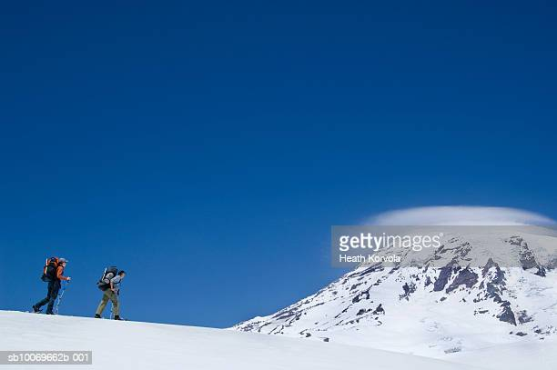 USA, Washington State, Cascade Mountains, two hikers walking on mountain ridge, side view