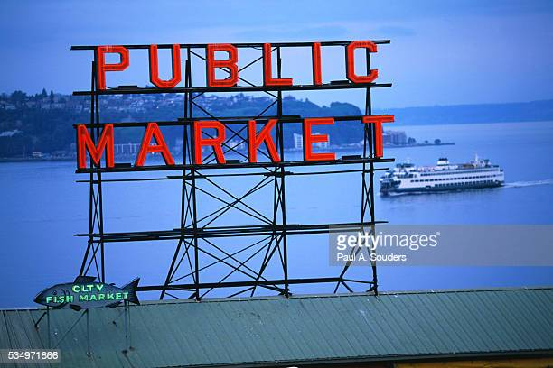 Washington State Ferry Sails Behind the Neon Public Market Sign in Seattle