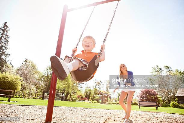 USA, Washington State, Seattle, Mother and son (2-3) swinging on swing in park