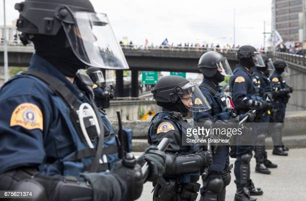 Washington State troopers block access to Interstate 5 as Workers and Immigrant Rights March participants pass by on May 1 2017 in Seattle Washington...