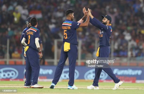 Washington Sundar of India celebrates after taking the wicket of Jason Roy of England with team mate Virat Kohli during the 1st T20 International...