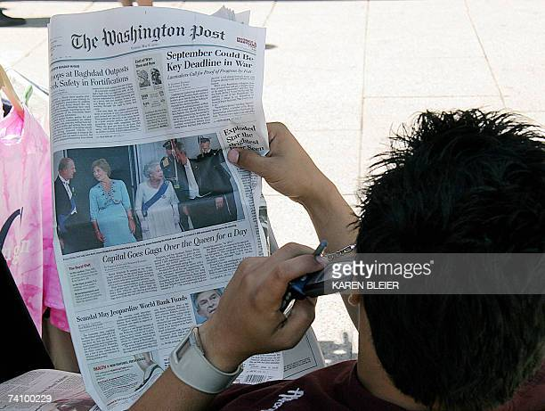 A man reads the Washington Post featuring the visit of Britain's Queen Elizabeth II and her husband Prince Philip 08 May 2007 in Washington DC...