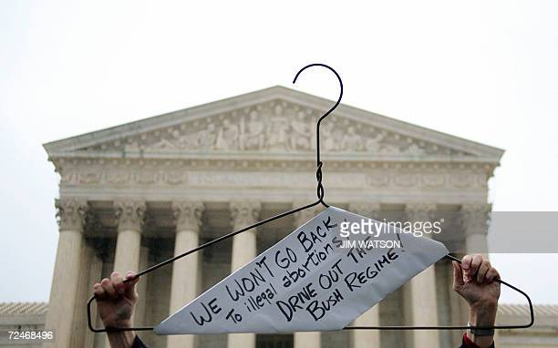 A prochoice demonstrator holds up a coat hanger symbolizing illegal abortions outside the US Supreme Court in Washington DC 08 November 2006 as the...