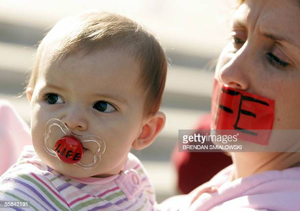 Washington, UNITED STATES: A pro-life activist holds a baby during a prayer rally outside of the US Supreme Court 03 October, 2005 in Washington, DC...