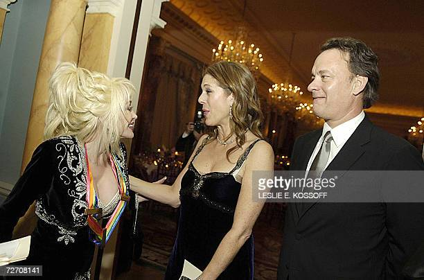 Actor Tom Hanks and his wife Rita Wilson congratulate Kennedy Center Honors recipients Dolly Parton after she received the award during a dinner...