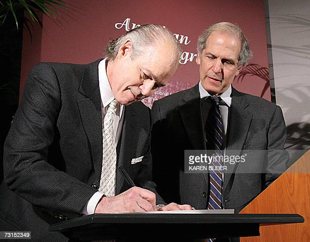 Dr Robert Jarvik developer of artificial hearts signs documents as Brent Glass director of the National Museum of American History looks on 30...