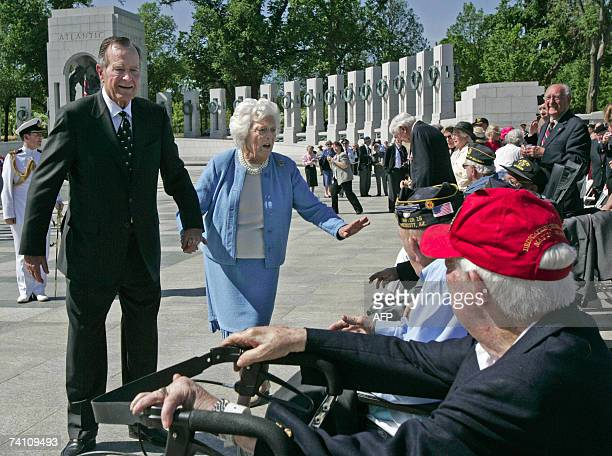 Former US president George HW Bush and his wife Barbara greet World War II veterans while visiting the World War II Memorial with Britain's Queen...