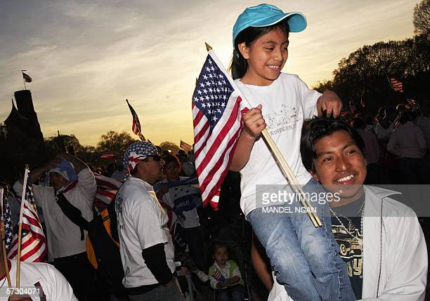 Immigration protestors hold US flags as they listen to speakers during an immigration rally on the National Mall 10 April 2006 in Washington DC The...