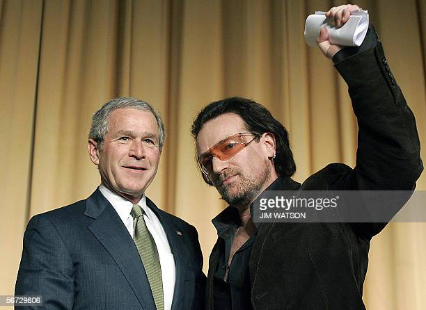 Lead singer of the Irish rock group U2 Bono gestures as he stands with US President George W Bush after speaking at the National Prayer Breakfast in...