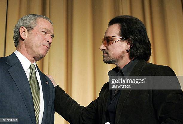 Lead singer of the Irish rock group U2 Bono places his hand on US President George W Bush's shoulder after speaking at the National Prayer Breakfast...