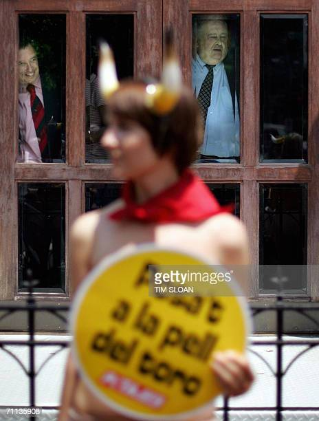 Men inside the Spanish Embassy watch nude protesters from the People for the Ethical Treatment of Animals during a demonstration 06 June 2006 in...
