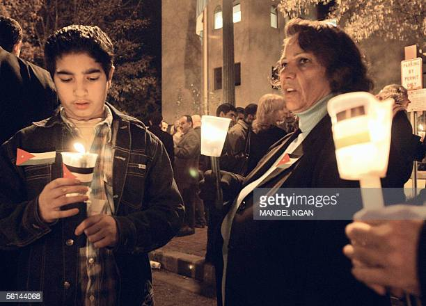 Mourners hold candles during a vigil outside the Embassy of Jordan 11 November 2005 in Washington DC The UN Security Council strongly condemned the...