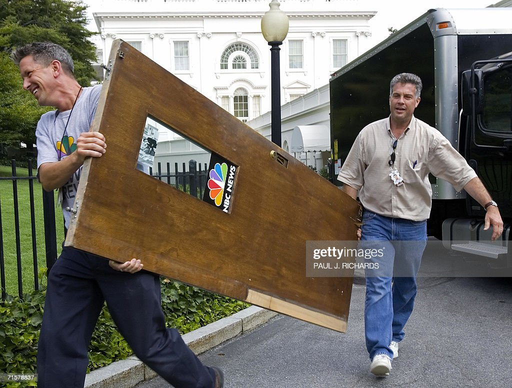 Television technicians Wesley Scruggs (L) and Steve Mitnick (R) conduct a special mission from NBC New's Tim Russert to deliver the door of the NBC news booth at the White House to him as NBC news pulls out of the presidential mansion 03 August 2006 in Washington, DC. Reporters who cover the White House are being evicted this week from their dingy, depressing digs in what was once the West Wing swimming pool area, for what is set to be a months-long renovation. AFP PHOTO/Paul J. Richards