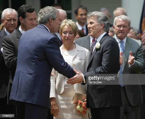 President George W Bush shakes hands with John Walsh as Walsh's wife Reve Sen Rick Santorum RPA and Rep Mark Foley RFL look on before the Signing of...