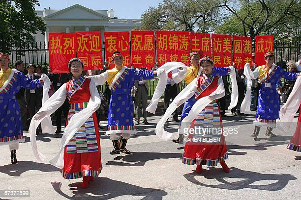Washington, UNITED STATES: Supporters of Chinese President Hu Jintao dance 20 April in front of the White House in Washington, DC. US President...