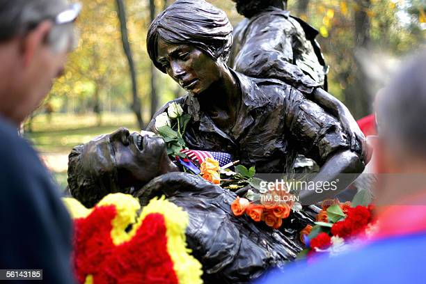 The Vietnam Women's Memorial is covered with roses and small US flags as hundreds of veterans and their families gather to commemorate Veterans Day...