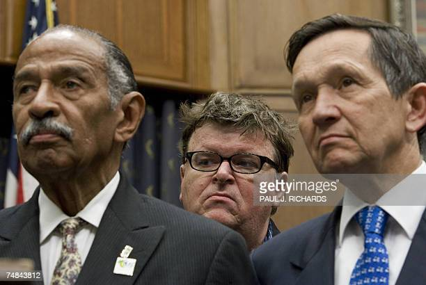 US movie maker Michael Moore listens to politicians as he stands behind US Repand US Presidential Candidate Dennis J Kucinich and Representative John...
