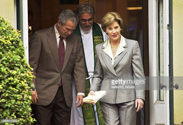US President George W Bush and First Lady Laura Bush are escorted by Reverend Luis Leon as they leave St John's Espiscopal Church in Washington 09...