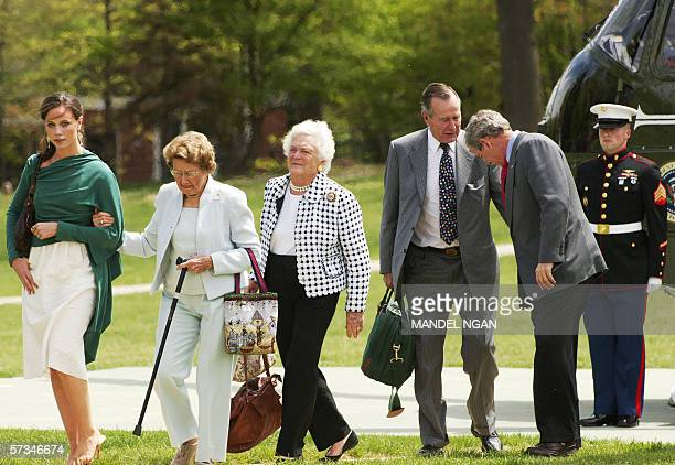 US President George W Bush chats with his father former president George HW Bush while making their way from Marine One with his daughter Barbara...