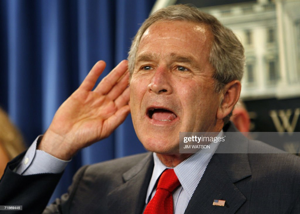 US President George W. Bush cups his ear after a question was shouted to him by the press while visiting during the final press briefing in the James Brady Press Briefing Room, at the White House 02 August 2006 in Washington,DC. The Briefing Room, as well as the press working spaces, are being renovated. While journalists have complained for years about the crowded, dirty conditions and the absence -- until actor Tom Hanks stepped in -- of a proper coffee machine, their chief fear is of not being allowed to return. White House spokesman Tony Snow, asked to address that concern on Wednesday, played off the fact that the blue-curtained briefing room was built over the swimming pool last used by a US president when Lyndon Johnson was in office. AFP PHOTO/Jim WATSON