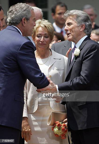 US President George W Bush shakes hands with John Walsh before Walsh's wife Reve before the Signing of HR 4472 the Adam Walsh Child Protection and...