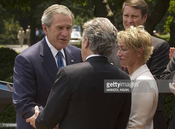 US President George W Bush shakes hands with John Walsh as Walsh's wife Reve looks on during the signing ceremony of HR 4472 the Adam Walsh Child...