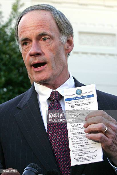 Washington, UNITED STATES: US Senator Tom Carper, D-DE, holds a copy of a Department of Defense report on Iraq 16 December 2005 outside the West...