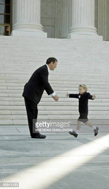 Washington, UNITED STATES: US Supreme Chief Justice John G. Roberts, Jr. Is greeted by his son Jack outside the Supreme Court 03 October, 2005 in...