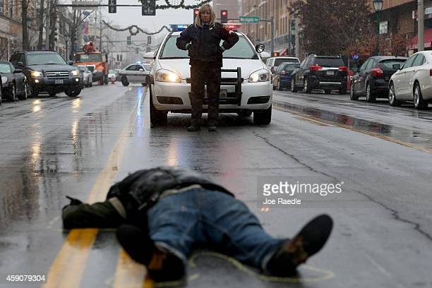 Washington University in St Louis police officer looks on as a demonstrator lays on the ground during a mock death protest of the shooting death of...