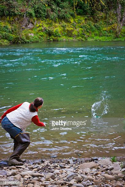 USA, Washington, Vancouver, Rear view of woman skipping stones on river