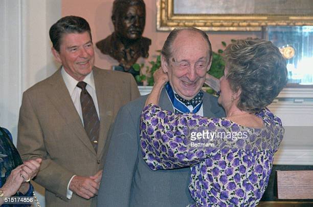 Vladimir Horowitz winces as Mrs Reagan places the Medal of Freedom around his neck President Reagan presented the medal to the pianist calling him an...