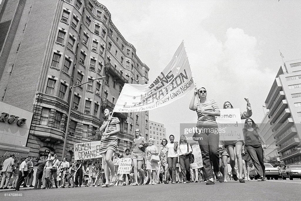 'Well dressed, happy young women carry their signs down Washington's Connecticut Avenue in their demonstration for equal rights. The group marched to Farragut Square for futher demonstrations.' Photograph shows marchers from a low angle, buildings in background.